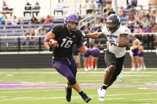 Clint Sigg of USF runs the ball after a reception as Devon Moore of Winona State pursues during Saturday's game in Sioux Falls.