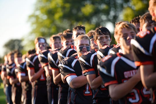 The Dell Rapids Quarriers stand for the national anthem on Friday night, September 13, in Dell Rapids.