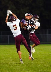 Dell Rapids Quarriers' Logan Ellingson catches the ball between two Madison Bulldogs on Friday night, September 13, in Dell Rapids.