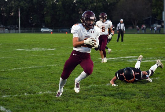 Mason Avery of the Madison Bulldogs runs the ball into the end zone, outrunning Dell Rapids' Tyler Wood on Friday night, September 13, in Dell Rapids.