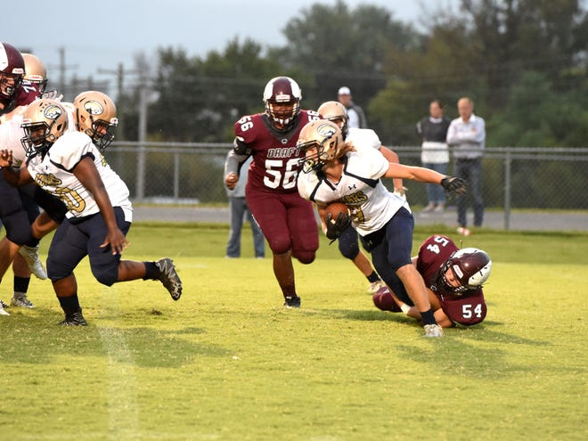 Stuarts Draft's Ethan Cash (54) grabs a Covington player before bringing him down in the backfield Friday night.
