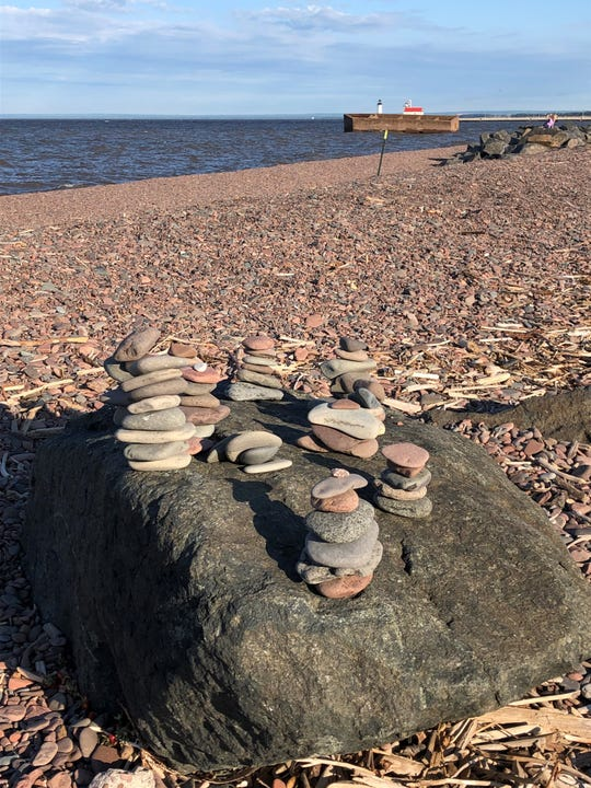Rock cairns left behind by some person or people are shown this summer on the shore of Lake Superior in Duluth.  Creation of these on public lands has sparked a debate nationwide.