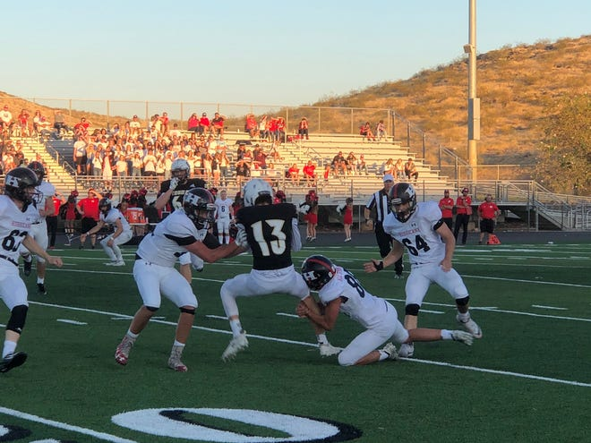 Desert Hills Thunder quarterback Logan Wilstead (13) being tackled by Hurricane's Luke Wright (88) during the Thunder's 40-25 win over the Tigers on Friday, Sept. 13, 2019.