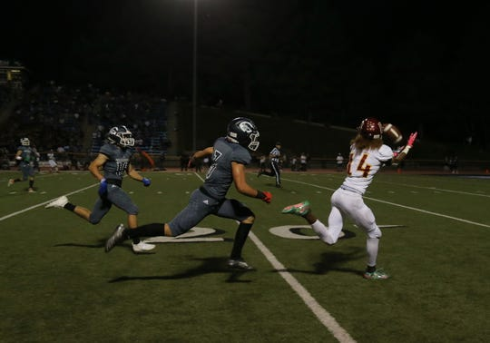 Oxnard High's Aaron Fontes makes a catch en route to a touchdown during the second quarter of the Yellowjackets' 26-25 loss to Camarillo on Friday night at Moorpark College.