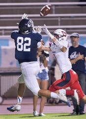 Redwood's Sam Olson, left, takes a pass under pressure from Tulare Western's Jose Valencia before scoring in non-league high school football on Friday, September 13, 2019.