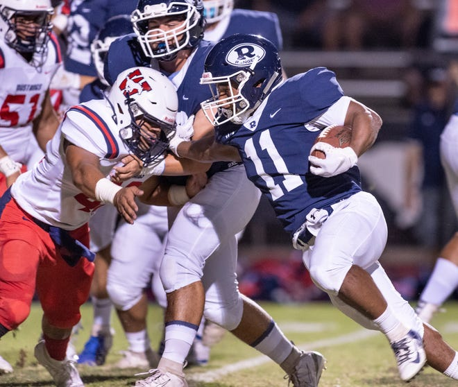 Redwood's James Richardson runs into a Tulare Western defender in non-league high school football on Friday, September 13, 2019.