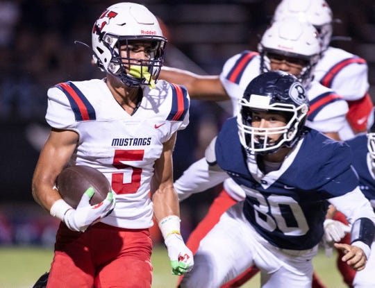 Tulare Western's Mikey Ficher runs ahead of Redwood's Alex Rodriguez in non-league high school football on Friday, September 13, 2019.