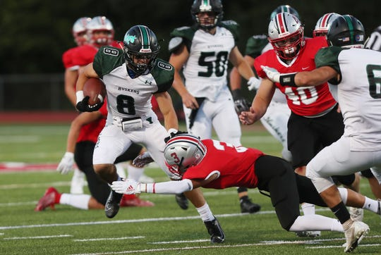 Yorktown's Dylan Smith (8) avoids a tackle from Somers' Anthony Gionta (3) on his way to a first half touchdown at Somers High School Sept. 13, 2019.