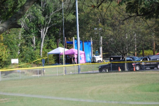 Investigators work at the scene where possible human remains were found near a softball field in Smyrna.