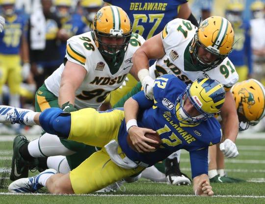 Delaware quarterback Pat Kehoe is sacked by North Dakota State's Matt Biegler (98) and Derek Tuszka in the first quarter at Delaware Stadium Saturday
