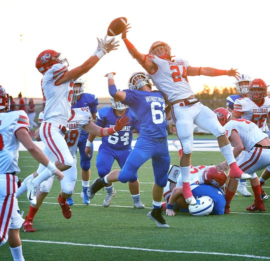 Holliday defenders Tucker Strealy (21) and Tristin Boyd (24) jump for a pass that was misdirected when Windthorst quarterback Cy Belcher was hit as he released the ball. Strealy caught the ball and ran in for Holliday's first touchdown of the night.