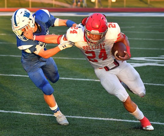 Holliday runningback Tristin Boyd (24) battles for more yardage against Windthorst defensive back Gage Gillispie (81) during second quarter action Friday night in Windthorst.