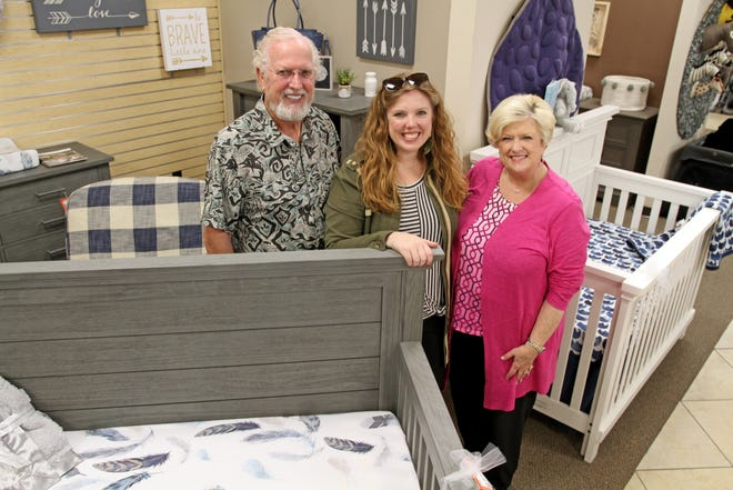 Storkland owners Doug Tritton, left, Anne McGaha and Joellen Tritton pose next to a crib Saturday, Sept. 14, 2019, during the store's 40th birthday party.
