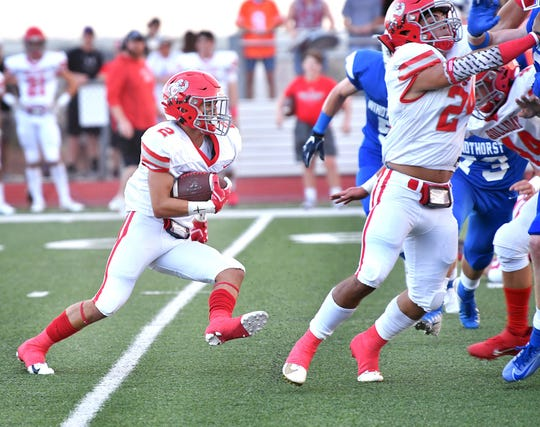 Holliday Eagles runningback Austin Jones (2) cuts inside behind blocking from Tristin Boyd (24) Friday night agasint Windthorst.