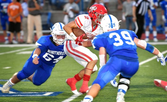 Windthorst's Eduardo Llamas (64) and Ethan Belcher (39) close in on Holliday ball carrier Austin Jones (2) earlier this season.