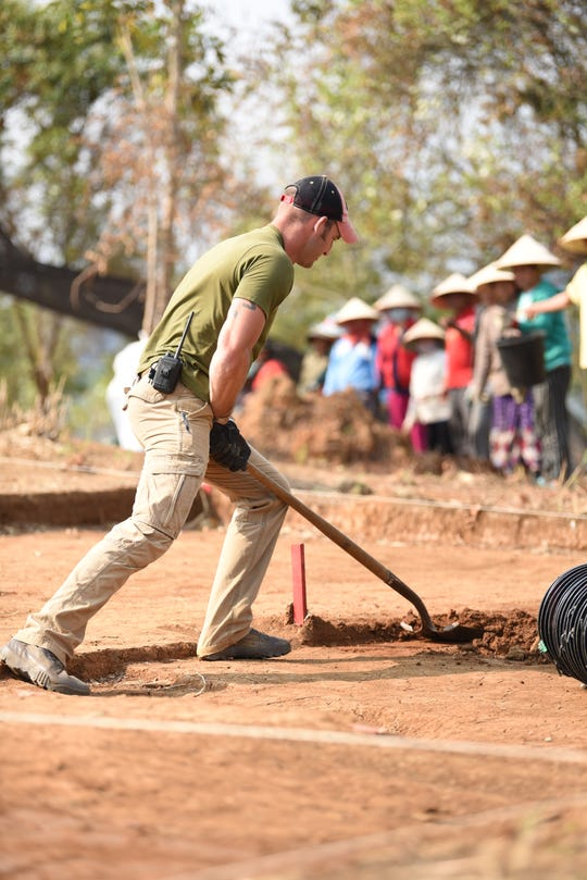 U.S. Army SFC Joshua Morse, a Defense POW/MIA Accounting Agency (DPAA) recovery team sergeant, pushes a square shovel along the floor of an excavation site on Feb. 11, 2019.