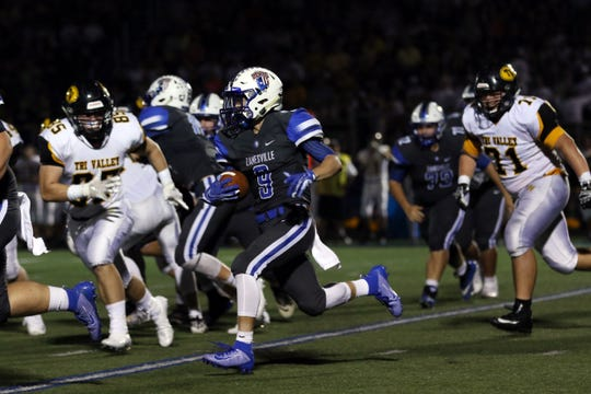 Zanesvilles Jordan Martin carries the ball against Tri-Valley Friday night at Zanesville.