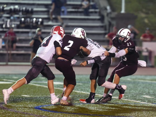 Sheridan quarterback Nate Johnson is tackled by John Glenn's Brady Emerson, left, and Ben Judd. Emerson made second team All-Ohio as a linebacker and contributed to all three phases for the Muskies.
