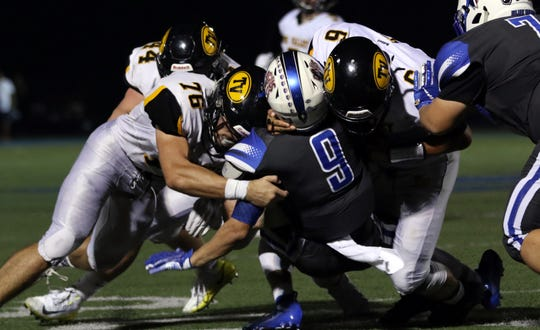 Tri-Valley's Gyle Bradshaw (76) Aiden Fritter (6) and Drew Richert (44) tackle Zanesville's Jordan Martin.