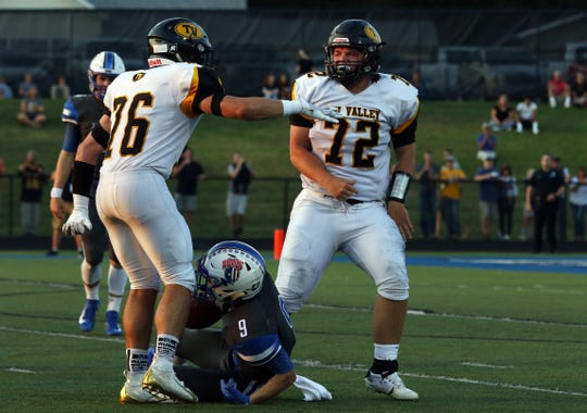Tri-Valley's Seth Tyson (72) and Gyle Bradshaw celebrate after tackling Zanesville's Jordan Martin. Bradshaw received our TR Prime Time Defensive Player of the Year honor.