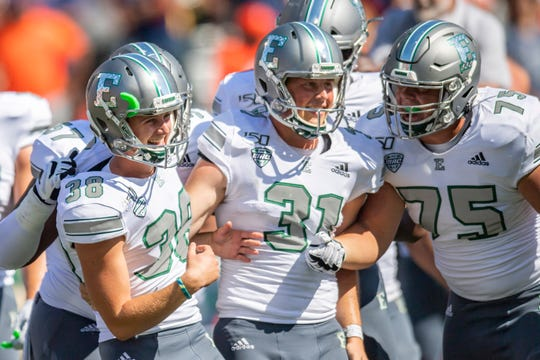 Eastern Michigan kicker Chad Ryland (38) celebrates with teammates after kicking the game-winning field goal against Illinois.