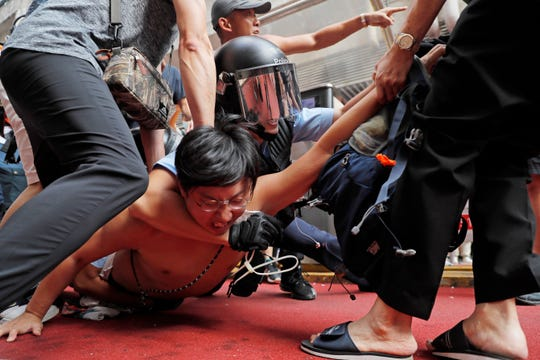 Police detain a man after fights broke out between pro-China supporters and anti-government protesters outside the Amoy Plaza in the Kowloon Bay district in Hong Kong, Saturday, Sept. 14, 2019. Skirmishes broke out Saturday at a shopping mall in Hong Kong between supporters of the ongoing protests for democratic reforms in the semiautonomous Chinese territory and people backing the central government in Beijing.
