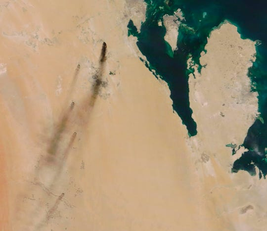 This Saturday, Sept. 14, 2019, satellite image shows fires following Yemen's Houthi rebels claiming a drone attack on two major oil installations in eastern Saudi Arabia.  The island shown in the image is Bahrain, while the peninsula in the image is Qatar.