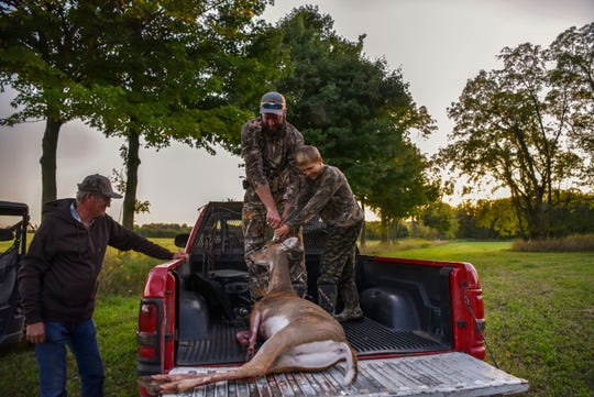 Jonathan and Easton VanMiddlesworth load Easton's first buck on Saturday, Sept. 14, 2019 in Climax, Mich. Jonathan grew up going hunting with his father, pictured left.