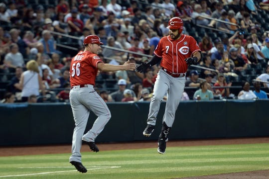 Sep 15, 2019; Phoenix, AZ, USA; Cincinnati Reds third baseman Eugenio Suarez (7) celebrates his solo home run against the Arizona Diamondbacks with Cincinnati Reds third base/catching coach J.R. House (56) during the fourth inning at Chase Field. Mandatory Credit: Joe Camporeale-USA TODAY Sports