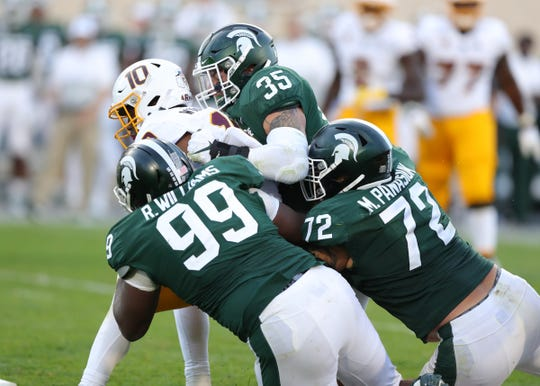 Michigan State Spartans' Joe Bachie (35) Raequan Williams (99) and Mike Panasiuk (72) tackle Arizona State's Kyle Williams during the second half Saturday, Sept. 14, 2019 at Spartan Stadium.