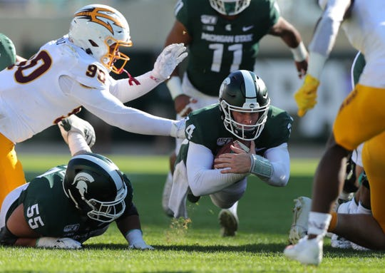 Michigan State Spartans quarterback Brian Lewerke dives for a first down against Arizona State during the first half Sept. 14, 2019 at Spartan Stadium.