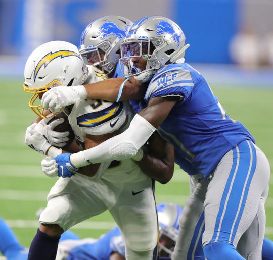 Detroit Lions safety Tracy Walker, front,  and linebacker Jahlani Tavai tackle Los Angeles Chargers running back Austin Ekeler during the second half Sunday Sept. 15, 2019 at Ford Field.