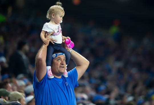 A Lions fan holds up a baby during the game against the Chargers at Ford Field, Sunday, Sept. 15, 2019. The Lions won, 13-10.