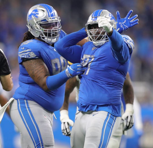Damon Harrison (98) and A'Shawn Robinson (91) celebrate after a sack in 2019.