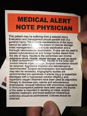"""This is a card UAW janitorial workers carry at Flint Assembly. They note their jobs require skill, workplace injuries """"parallel"""" """"gunshot injury."""""""