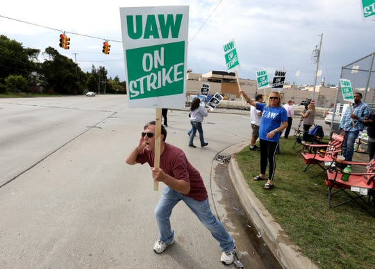 Jack Barber, 57, of Clio leans out looking to get honks from passing cars for support as he and other UAW members from Locals 598 and 659 strike prior to the union leadership authorizing the autoworker strike in front of the General Motors Flint Assembly plant in Flint, Michigan on Sunday, September 15, 2019.