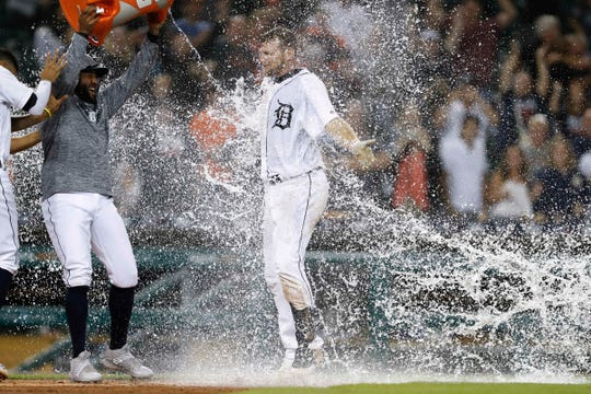 The Detroit Tigers' John Hicks gets doused with water by Ronny Rodriguez after hitting a grand slam in the 12th inning.