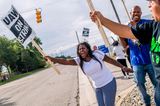 Flint resident Dorrit Madison, who has worked at the plant for more than 11 years, shouts out at cars passing by as General Motors employees demonstrate outside of the Flint Assembly Plant on Sunday.