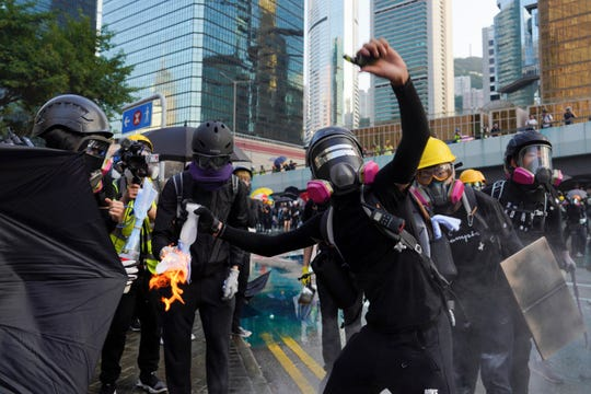 An anti-government protester throws a Molotov cocktail during a demonstration near Central Government Complex in Hong Kong, Sunday, Sept. 15, 2019.
