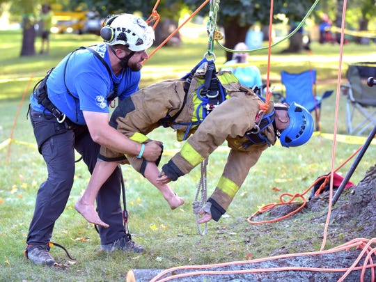 """Jordan Lynch, 31, of Mattawan positions a dummy he """"rescued"""" during the 25th Michigan Tree Climbing Championship Saturday in Traverse City."""