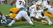 Arizona State's Eno Benjamin (3) stretches out for the game-winning touchdown as MSU Joe Bachie (35) and Xavier Henderson (3) try to stop the running back.