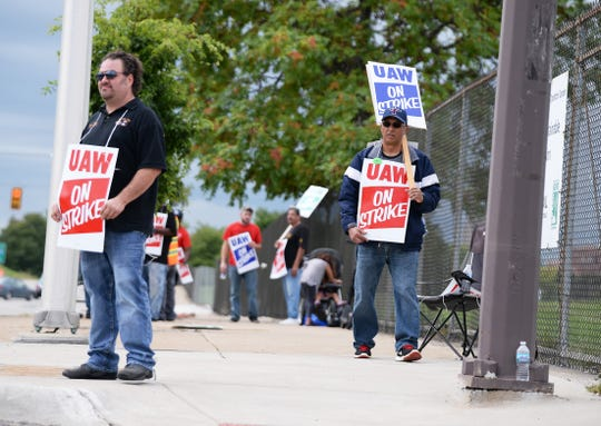 GM-Detroit-Hamtramck assembly plant auto workers Mike Mucci, left, and Eddie Mendoza, both members of UAW Local 22, walk the picket line in front of the plant Sunday afternoon.