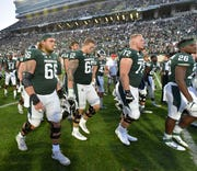 MSU players are dejected as they walk off the field after their loss.
