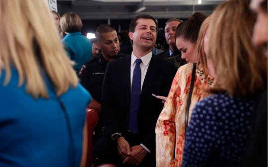South Bend Mayor Pete Buttigieg, center, works his way through the media in the spin room following the Democratic presidential primary debate hosted by ABC on the campus of Texas Southern University in Houston on Sept. 12, 2019.