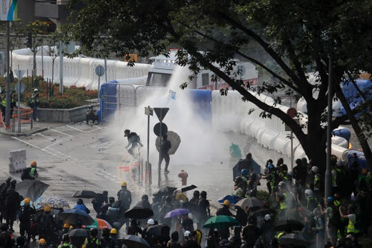 Anti-government protesters are sprayed by water cannon during a demonstration near Central Government Complex in Hong Kong, Sunday, Sept. 15, 2019. P