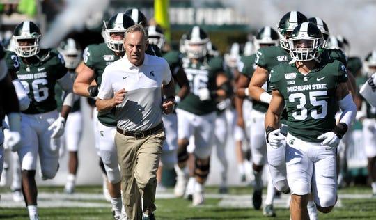 MSU head coach Mark Dantonio leads his Spartans onto the field Saturday.