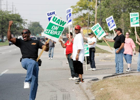 Randolph Walker cheers on motorist as they blow their horns in support of the strike at GM's Powertrain Plant in Warren in 2007.