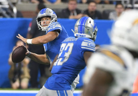 Lions' Matthew Stafford pulls back for a long pass in the third quarter.