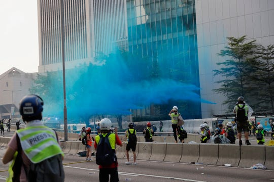 Police vehicle sprays blue-colored water towards anti-government protesters during a demonstration near Central Government Complex in Hong Kong, Sunday, Sept. 15, 2019.