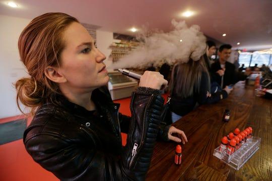 Talia Eisenberg, co-founder of the Henley Vaporium, uses her vaping device in New York.